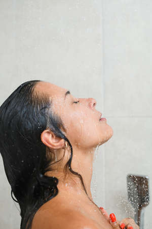 Young female half face portrait during take shower, remove shampoo from wet skin and hair with closed eyes, enjoy bathing at home, close up. Stock fotó