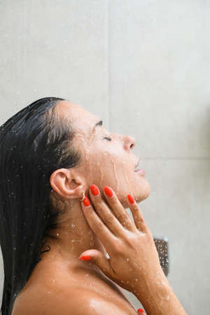 Brunette girl with red manicure polish take shower, bath with tiles background, wash face, hair and neck with gel and water close up. Stock fotó