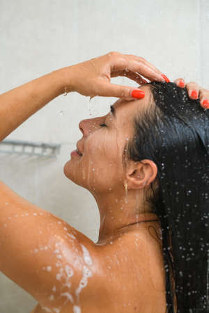 Side portrait of young beautiful brunette woman take bath, shower, raise head up under faucet to wash neck, face and hair with water drops and foam. White tiles bathroom.