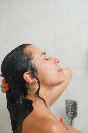 Young female half face portrait during take shower, remove soap from wet skin, face, hair with closed eyes, enjoy bathing at home. Stock fotó