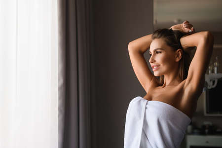 Attractive female portrait with hands raise up, morning stretching at appartment after spa, shower, in beautiful morning light. Happy sexy lady wrapped in white towel indoors. Stock fotó