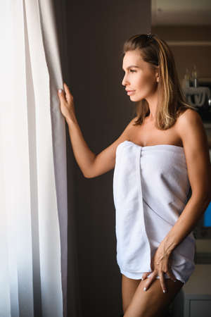 Beautiful lady open window blackout curtains, morning light, wrapped in white short towel, show legs and neckline, luxury life.