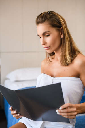 Portrait of attractive woman wearing white towel after shower, open and read about hotel breakfast restaurant menu.