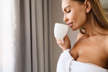 Beautiful young woman with soft skin near window with cup of tea, coffee after shower, wearing white towel, with gray curtains on background. Face of sensual blonde female at happy morning.