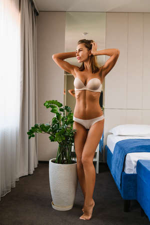 Fit female in white bra and panties full length at morning near bed looking at window, barefoot on toes. Sexy woman with beautiful body at home.