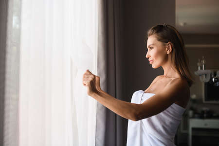 Beautiful lady wearing white towel after shower, open window cover curtains to see morning sun light, enjoy moment at home. Stock fotó