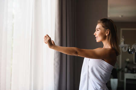 Beautiful woman wearing white towel after shower, open window cover curtains to see morning sun light, enjoy moment at luxury hotel.