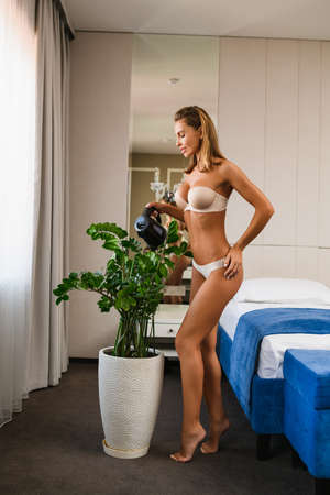 Sexy look of female wearing white underwear with jar watering big home plant at vase. Good morning with seductive lady housewife at bedroom near window. Stock fotó