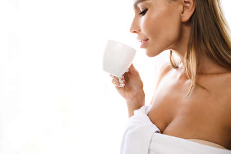 Full of light portrait of seductive tanned girl with soft skin in white towel, going to drink from small cup. Beautiful morning.