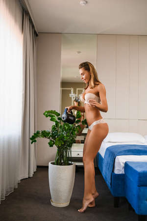 Seductive blonde girl with nice butt in underwear stay full length on toes at bedroom. Watering flowers in front of window. Stock fotó