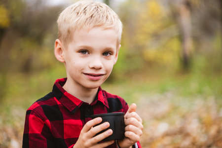 Preteen blonde male child in red shirt holds black bottle cup with hot beverage. Happy family weekend at autumn park.