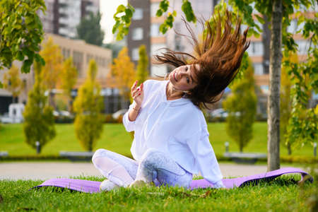 Cute brunette sportive girl in white hoodie sitting at mat on city park background with headphones and dance, move her head and hair