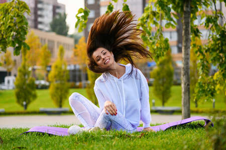Smiling sportive brunette girl sit at mat in white clothes, listen music in earphones with action at green city park background