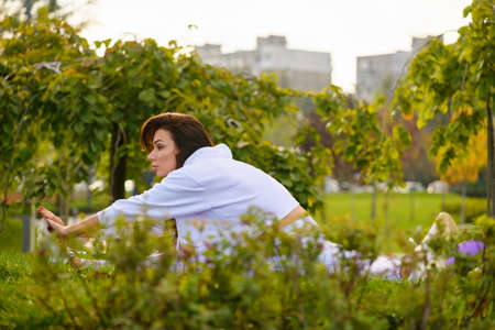 Brunette girl making morning workout fitness at beautiful green park nature, sitting on mat in twine and stretch hands