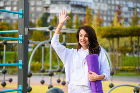 Smiling brunette sportive woman at playground with purple mat greeting, welcoming somebody with hand up