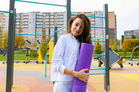 Sportive brunette female posing with purple mat for exercises, workout, fitness, yoga at playground in city park Banco de Imagens
