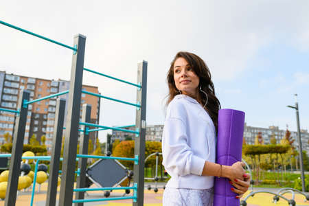 Brunette sportive girl wear headphones, white hoodie, hold purple mat and posing at city park for workout fitness exercises, low angle view