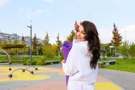 Sportive brunette woman in white hoodie hold purple mat at city park playground, workout, fitness, stretching outdoors