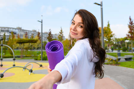 Young brunette woman in white hoodie, holding purple sport mat at city park background, turn back, hold my hand, follow me trend idea