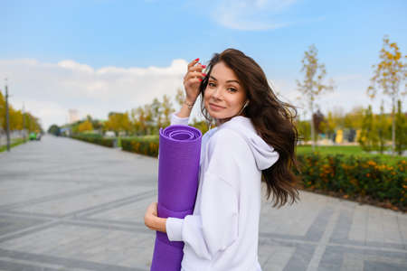 Brunette young woman in white sportswear with earphones hold purple mat and looking back at city park background Banco de Imagens