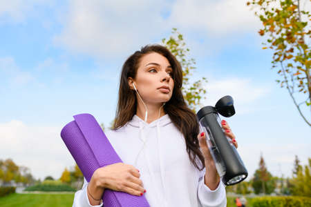 Sportive brunette female at green city park background with purple mat, wear headphones, drink water after workout, fitness, yoga outdoors