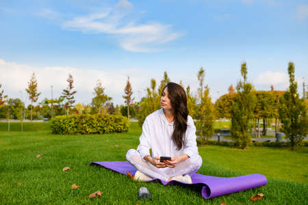 Beautiful brunette female sit on purple mat at green city park, hold phone and relax after workout, gymnastics
