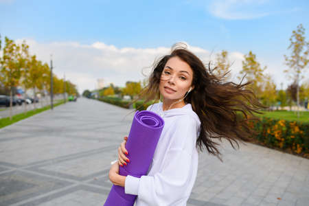 Beautiful brunette walk in city park, wearing white hoodie with purple mat after outdoor workout, stretching, fitness and looking back with hair fly