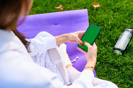 Sportive girl sit on mat, hold phone with blank green screen, drink water from bottle after workout, fitness outdoors