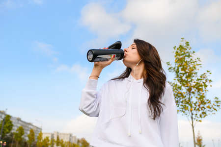 Low angle shot of attractive girl in white hoddie and headphones hold bottle up and drinking water after workout, stretching, fitness outdoors