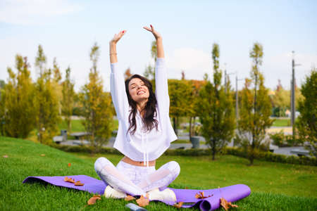 Attractive brunette girl in white sportwear sit on purple mat in lotus pose and stretch up hands under head, outdoor fitness, yoga exercises Banco de Imagens