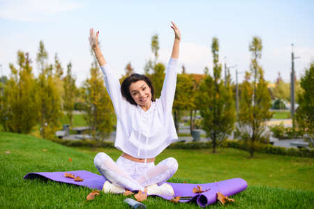 Beautiful brunette sit on sport mat in lotus pose, raise hands up with closed eyes during workout, stretching, yoga at city park Banco de Imagens