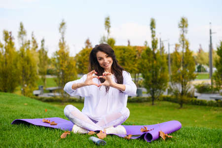 Beautiful girl in white clothes sit at sport mat in lotus pose and put fingers in heart shape, love fitness, yoga, workout concept outdoors