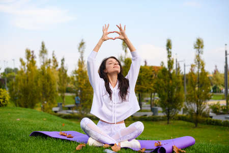 Attractive girl in white sportswear make fingers mudra yoga with hands raised up, sitting on mat at city park, workout outdoors Banco de Imagens