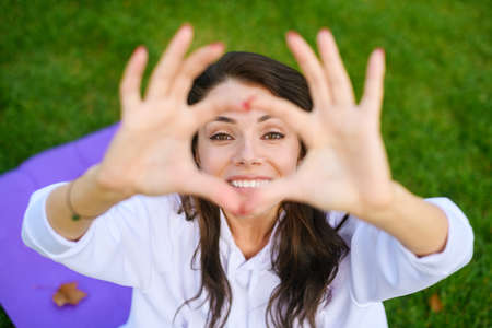 Beautiful girl sit on mat at green park, raise hands up in yoga mudra position and look smile though fingers