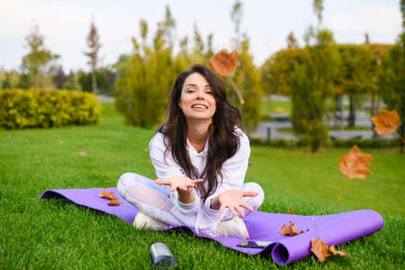 Pretty brunette young woman sit at sport mat with crossed legs and play with dry leaves at city park during fall