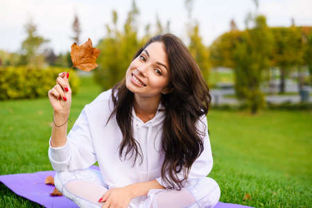 Beautiful young woman sit at sport purple mat in city autumn park, take and look at one dry leaf after workout outdoors Banco de Imagens