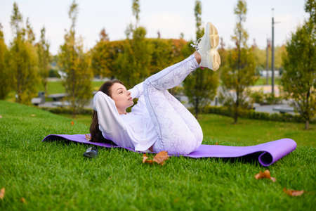 Sporty female in white clothes lay at mat outdoors and make stretching, fitness, abs crunches at nature background