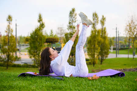 Beautiful fit female lay at sport mat and make abs crunches, pull ups and stretching in green city park