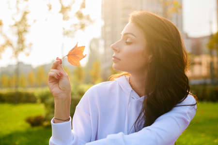 Beautiful brunette girl in white hoodie sit at green city park, hold one autumn leaf in soft sun light