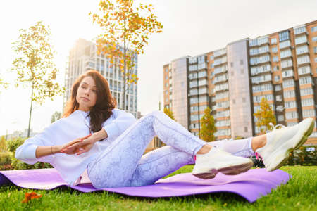 Beautiful brunette female lay at sport mat in white sportswear, making abs crunches, fitness, yoga stretching exercises with modern city buildings behind Banco de Imagens