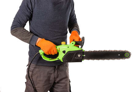 Male sawyer hands in orange protective textile gloves carry new electric saw at isolated white background