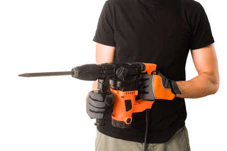 Male hands in protective gloves holding new big electric perforator with long drill and handle at isolated white background Banco de Imagens