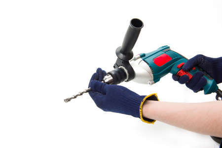 Man in protective gloves change drill in electric perforator at cut out isolated background, construction, renovation, repair tool