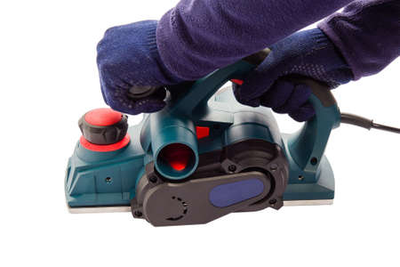 Male hand with an electric jointer plane. Male master hands wearing gloves on isolated white background.