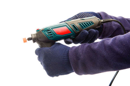 Two male hands in navy blue protective gloves holding perforator with nozzle for grinding and polishing at isolated white background.