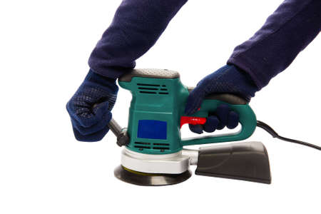 Man in protective blue gloves hold handles of eccentric orbital sander machine at isolated white background