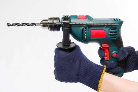 Male hands are holding an electric drill. Hands in blue gloves. Drill on a white background. Banco de Imagens