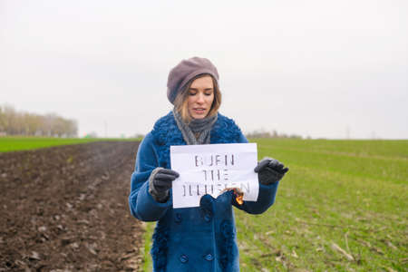Beautiful frustrated girl in blue coat stay at open area with burned paper and printed words burn the illusion