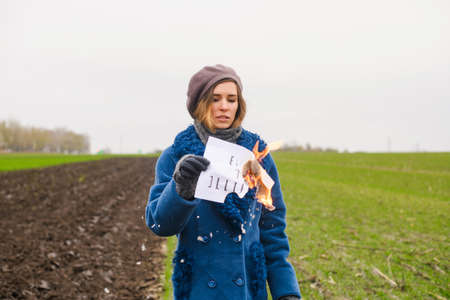 Desperate woman in blue coat and beret stay at open area with smolder paper and printed text words Burn the illusion