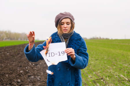 Young strong desperate woman in blue coat and beret hold burning paper with printed word Covid-19 at isolated place
